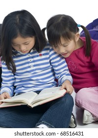 Two young asian girls reading a book