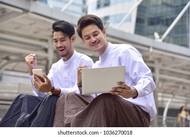 Two Young asian handsome businessman smiling while reading his tablet  in myanmar