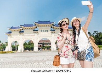 "Two young Asian ladies taking a selfie in the front of the long historical building, Chiang Kai-shek Memorial Hall. Translation on decorated archway text ""freedom square""."