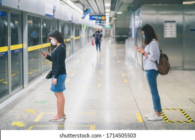 Two young asian woman wearing protective face mask stand in line with social distancing during waiting train in subway due to Coronavirus or COVID-19 outbreak situation in all of landmass in the world