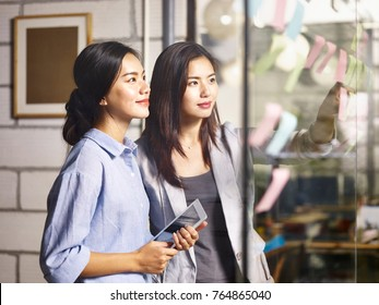 two young asian women entrepreneurs discussing business plan in office using sticky notes.