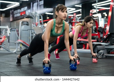 Two Young Asian women push-ups on kettle ball in crossfit gym.