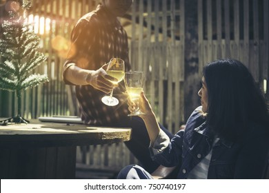 Two young Asians are smash a glass of wine in celebration of Christmas. Both people happily drink in a warm atmosphere. There are shows, evening sun penetrates inside the barn, where they drink.