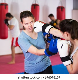 Two young athlete girls practicing boxing sparring at box class