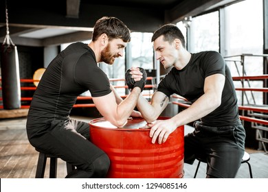 Two young athletes in black sportswear having a hard arm wrestling competition on a red barrel in the gym