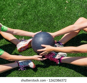 Two young athletes are passing a medicine ball back ond forth while doing situps on a green turf field.