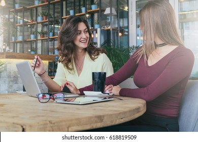 Two young attractive business women are sitting in cafe at table and talking.On table is laptop,cup of coffee, tablet computer and glasses. Girls working online, learning, shopping, blogging.Teamwork.