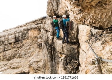 two young attractive male mountain climbers on very exposed Via Ferrata in Alta Badia in the Italian Dolomites