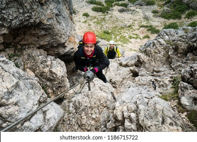 two young attractive mountain climbers on a steep and exposed Via Ferrata in Alta Badia in the South Tyrol in the Italian Dolomites