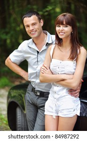 Two young attractive people: beautiful brunette woman and handsome man standing near car at summer green park.