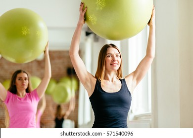 Two young attractive sporty women holding green fitness ball above head while doing pilates or yoga exercise at fitness studio.