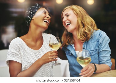 Two young attractive vivacious multiethnic female friends celebrating and laughing together over a glass of white wine