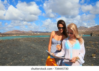 Two young attractive women with land map in summer holiday outdoor