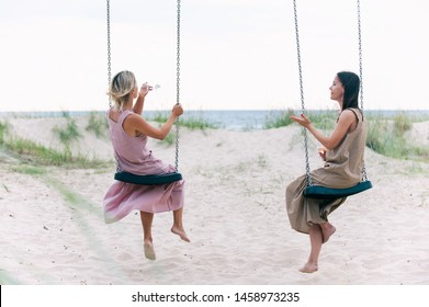 Two young attractive women resting on seesaw and drinking white wine on the beach. Friends/sisters. Summertime outdoors inspirational horizontal image. View from background