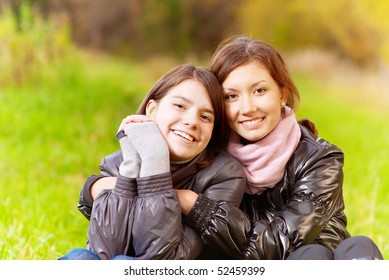 Two young attractive women's portrait on autumn background.
