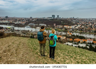 Two young backpackers enjoying view of Prague city skyline and Vltava river,Czech Republic.Attractive landscape with deep valley,hiking trails,Prague panorama in background.Active citylife style. - Shutterstock ID 1954307731