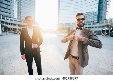 Two young bearded blonde and black hair modern businessman, posing outdoor in the city back light wearing sunglasses - working, successful concept