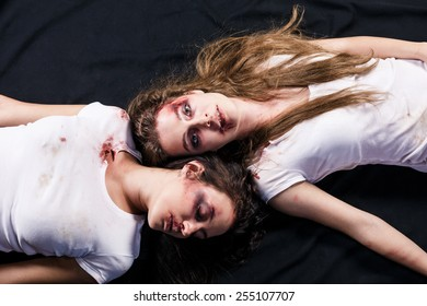 Two young beaten women with cuts and bruises lie down on the floor on black background