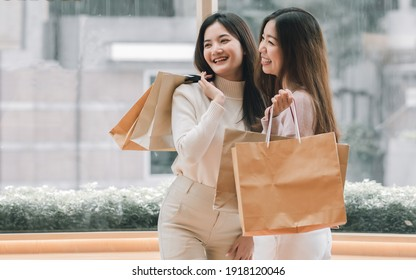 Two young beautiful asian women holding paper shopping bags and smiling. Lifestyle and Sales Discount Concept.