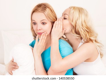 two young beautiful blond sisters whispering to each other in the bedroom at home