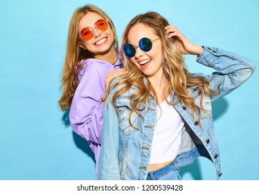 Two young beautiful blond smiling hipster girls in trendy summer clothes. Sexy carefree women posing near blue wall in sunglasses. Positive models going crazy