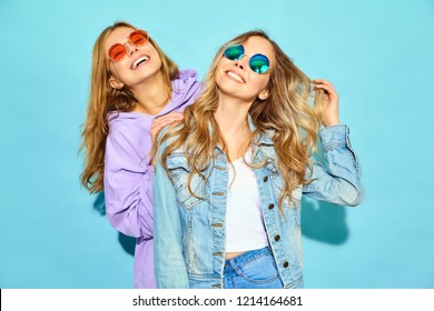 Two young beautiful blond smiling girls in trendy summer clothes.