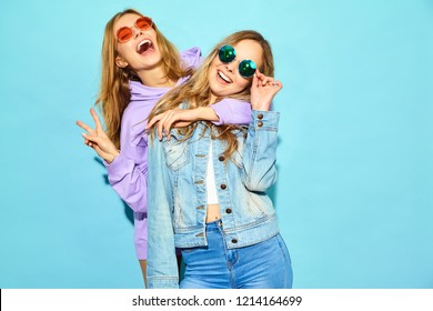 Two young beautiful blond smiling hipster girls in trendy summer clothes. Sexy carefree women posing near blue wall in sunglasses. Positive models going crazy and hugging