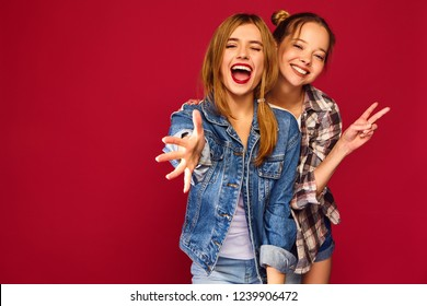 Two young beautiful blond smiling hipster girls posing in trendy summer checkered shirt clothes. Carefree women isolated on red background. Positive models going crazy and hugging