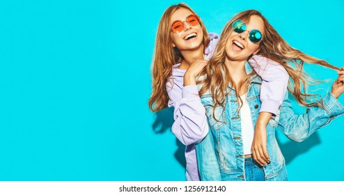Two young beautiful blond smiling hipster girls in trendy summer clothes. Sexy carefree women posing near blue wall in sunglasses. Positive models