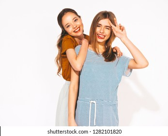 Two young beautiful blond smiling hipster girls in trendy summer casual clothes. Sexy carefree women isolated on white. Positive models going crazy