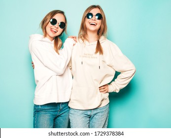 Two young beautiful blond smiling hipster girls in trendy summer hoodie clothes. Sexy carefree women posing near blue wall. Trendy and positive models having fun in sunglasses