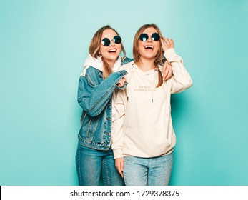 Two young beautiful brunette smiling hipster girls in trendy summer hoodie and jeans jacket clothes. Sexy carefree women posing near blue wall. Trendy and positive models having fun in sunglasses