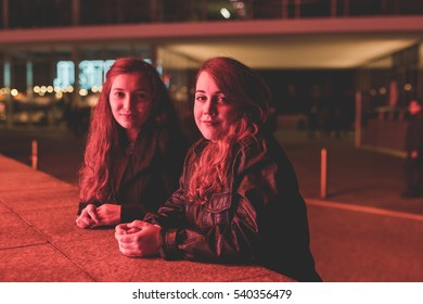 Two young beautiful caucasian women friends outdoor in the city night posing looking at camera smiling, illuminated by red light - happiness, serene, carefree concept
