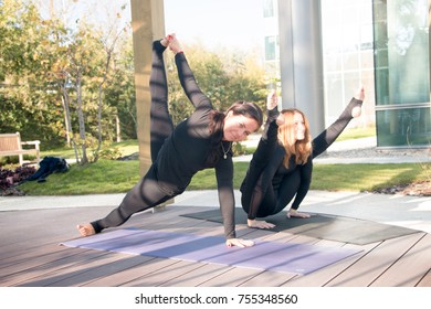 Two young beautiful caucasian women stretching outdoor in a city park in sunny day
