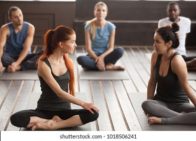 Two young beautiful fit yogi women talking at group training class, pilates instructors trainers discussing yoga exercises before session sitting on mats in gym studio with multiracial diverse people