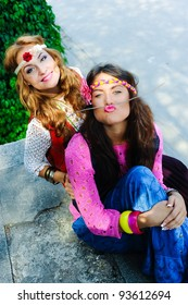 Two young beautiful funny  girls of hippie sit in the street
