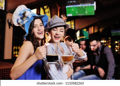 two young beautiful  girlfriends in Bavarian hats on the background of a bar holding a beer watching football on a TV monitor during the celebration of Oktoberfest