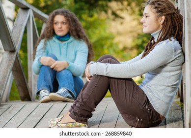 Two young and beautiful girls at banisters of little bridge in city-park.