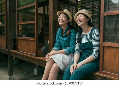 Two young beautiful girls in denim wears and straw hats sitting on steps talking and laughing. female friends relaxing outdoors in Tokyo Japan. smiling women enjoy garden view from old wooden house