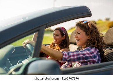 Two young beautiful girls driving in a convertible while smiling