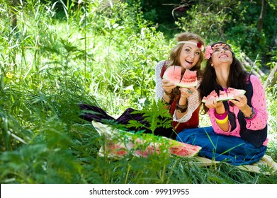 Two young beautiful girls eat a water-melon on a lawn