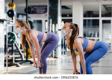 Two young beautiful girls exercise in the gym wearing masks during the pandemic. Social distancing in public places.