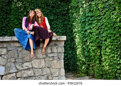 Two young beautiful girls of hippie sit in the street