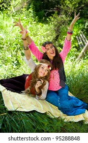 Two young beautiful girls hippie have fun laying in a lawn