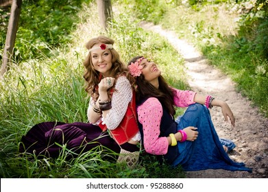 Two young beautiful girls   hippie have a rest on a lawn