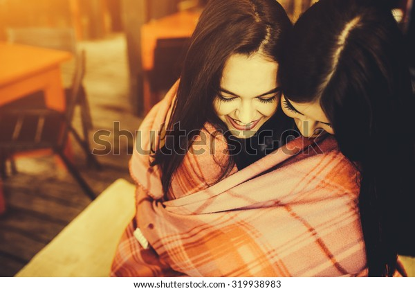 Two young and beautiful girls holding each other and having fun in cafe