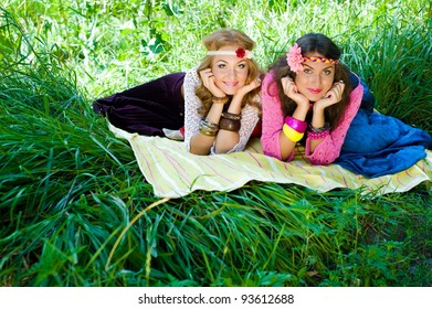 Two young beautiful girls lay on a grass in  a wood