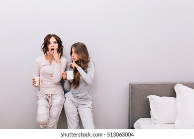 Two young beautiful girls in pajamas with cups having fun in sleeping room on grey wall background. Girl with curly hair looks astonished to camera