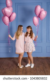 two young beautiful girls in pink dresses stand on a blue background and hold in their hands balls of heart