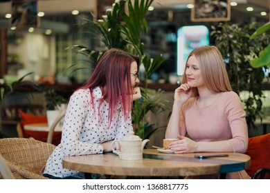 Two young beautiful girls sit in a green cafe at a table. Drink tea with croissants, chatting, laughing and taking pictures on a smartphone. The concept of communication and meeting with friends.